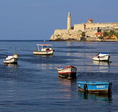 A lighthouse and a fortress, fishermen's boats, Havana harbour.
