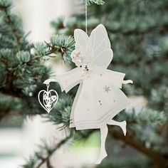 A silver metal and white paper laser cut Fairy decoration designed by Jette Frolich.
