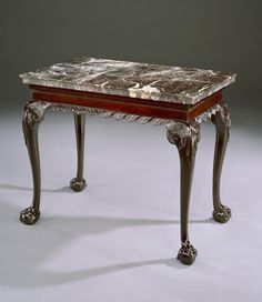 A superb mid 18th century Chippendale period carved mahogany side table, retaining the original rectangular 'Belgian Grey Saint-Anne' marble top with moulded edge above a concave frieze with gadrooned apron; on cabriole legs with acanthus clasp to the knees, terminating in ball and claw feet.   English, circa 1750