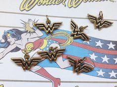 The princess of the Amazons is here to keep your jewelry collection fashionable. Wonder Woman Logo Charms feature a lovely gold color in the shape of the Wonder Woman logo. Use them on charm bracelets, to adorn necklaces, or to make adorable earrings. Materials: Metal Alloy Dimensions: Length: 3/8 Width: 7/8 Ring Diameter: 3/16 Contains 1 charm