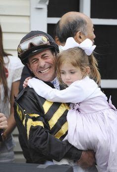 Jockey Gary Stevens, left, holds his daughter, Madison, after winning the 138th Preakness with Oxbow.
