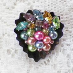 This is a one of a kind brooch. It features vintage bits and pieces of jewelry assembled into a little vintage tartlet/chocolate/butter tin.