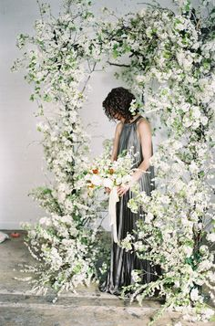Floral arch with bouquet and model at Sarah Winward workshop, film photography, fuji 400h, fine art photography, fine art flowers, florist, floral designer, floral design, floral stylist, silk ribbon, model, bride, blossom, white, green, orange, yellow, spirea, ranunculus, hellebore, foxglove, hyacinth, lilac, fritillaria. Photo by Chikae O-H