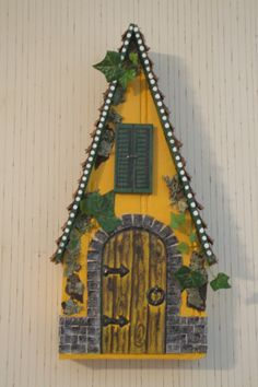 """Fairy House made to hang on a wall. Approx. 12"""" tall. Made with some natural materials: pine cones, lichen, and bark."""