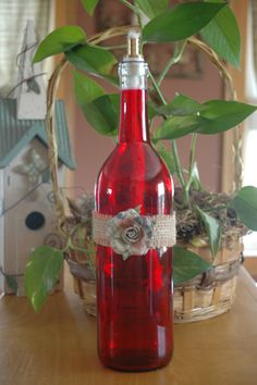 This red wine bottle tiki torch is wrapped in a burlap strip with a beautiful paper flower. This candle would be a great addition for your patio, porch or any table outside! This candle comes with a tiki torch wick for outdoor use only! Fill with citronella oil.