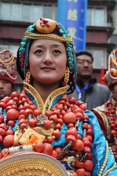 Government Celebrations in Kangding, Kardze, Tibet 2010   A Khampa Tibetan woman in a traditional ceremonial costume from Palyul county. She wears the traditional women's headdress in Palyul with many strands of turqoise, and a gold necklace across her forehead. The costume and ornaments are probably the belongings of her family, and contain much of the family's wealth and savings.