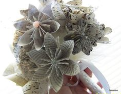 Book page and sheet music keepsake bouquet, a 12 flower handmade bouquet which features extra bling, and is sure to impress at your wedding or celebration. The neutral colors make a very big statement, and this keepsake bouquet will be a lasting memory of your celebration.    Each flower measures from 3-5 inches in diameter, and as the photos depict there is a random selection of vintage sheet music flowers and book page flowers. a small number of the origami kusudama flowers are solids with…