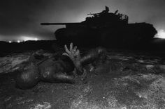 KUWAIT. Next to a tank destroyed by US aerial bombing, a dead Iraqi soldier is mumified by drops of oil escaping from wells, set on fire by the soldier's unit before it retreated. Magnum Photos Photographer Portfolio