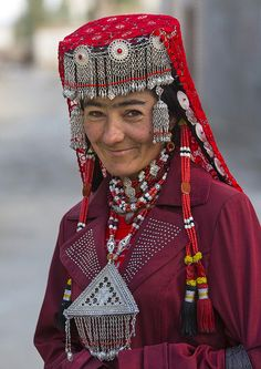 "Tajik woman in Tashkurgan, Xinjiang, China  by Eric Lafforgue on Flickr            (Larger), then click again    The photographer says: ""Most of the ones I met wore  some beautiful hats and necklaces. I asked why she had  those decorations, she answered it was her daily clothes!"