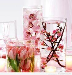 Decoración de centro de mesa con flores de cerezos y tulipanes sumergidas en agua