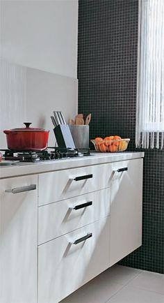 """Visual leve e prático. """"Queria uma cozinha clean, inspirada nos ambientes italianos"""", diz Rozana. Os armários são de MDF e laminado (Marcenaria Pais e Filhos). Já a bancada é de porcelanato. Esse material recobre a faixa de 60 cm sobre o fogão, que facilita a limpeza de gordura. Uma das paredes recebeu pastilhas de vidro (Pastilhart) e as demais, tinta acrílica (Suvinil)."""