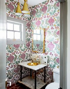 Purple and teal wallpaper in bathroom with gold sink and gold light fixture