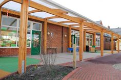 This timber canopy creates a sheltered play space area alongside an existing classroom building.