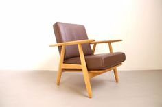 The GE-240 by Hans wegner, made by Getama is better known as the cigar chair because of the shape of the armrests. The frame is in solid oak and upholstery is brand new brown leather on this one.