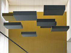 Acoustic ceiling clouds that provide sound insulation in a neat contemporary way.