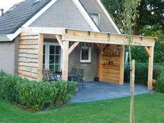 Veranda van douglas hout met licht door latende polycarbonaatplaten De veranda bestaat uit 15 bij 15 staanders gedeeltelijk betimmerd met lariks schaaldelen