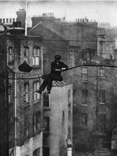 """1930s, telephone engineer, Mayfair, London. """"Twice a year the wires which support London's phone cables – each cable may hold the lines of thirty subscribers – are inspected. The cables are fastened to the wires by rawhide suspenders, and this man is detaching the thick dark cable from the old wire and fastening it to the new wire [that also supports the worker]. He sits in a """"bo'sns chair"""" consisting of a board slung by a loop at either end, which is fastened to the wire."""""""