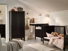 Simple A nursery with a cot changing table and wardrobe all in black brown