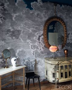 Barnaba Fornasetti [Fornasetti's Nuvole wallpaper by Cole & Son, chair with a Corinthian-column back, 1950s chest of drawers; Antonangeli Illuminazione table lamp, and Italian gilt-wood mirror.]