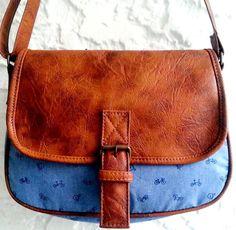 Bolsa tiracolo em tecido jeans dublado 100% algodão e tampa em couro ecológico chocolate <br> <br>Ferragens ouro velho <br>Bolso com zíper na parte das costas e no forro interno <br> <br>Bolsa ideal para aqueles dias em que você quer sair levando somente todos os itens essenciais!!!! <br> <br>Tamanho <br>Altura: 21 cm <br>Largura : 28cm <br>Profundidade: 10 cm