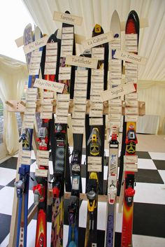 what a great idea! wedding placecards tacked on skis - each table is assigned name of great ski mountain or run