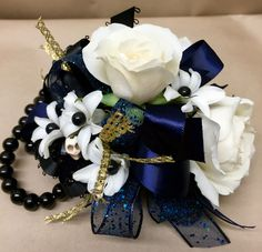 a wrist corsage featuring white tea roses and white ranunculus, blue ribbon, gold ribbon, black pearl pin accents and a skull bead – 37.95 - http://www.leighflorist.com #prom #promgflowers #leighflorist