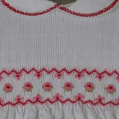 Pink and dark rose smocking on white. Featherstitch on collar.