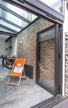 Aluminium folding doors | contemporary glass sleek glass roof to side extension | natural light | feature internal brick wall | industrial | modern architecture | Brighton Architects
