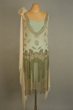 JEWELED FLAPPER DRESS with BEADED FRINGE, 1920s. White chiffon with deep U neckline front and back trimmed with a wide band of pearl, rhinestone and crystal bead medallions, wide jeweled hip band with graduated long beaded fringe, chiffon flower and drape at left shoulder, attached aqua underdress