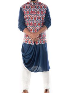 Featuring a royal blue cowl drapped kurta with a printed bandhgala waistcoat and a white churidar. The waistcoat has a beautiful floral print. Mens Indian Wear, Mens Ethnic Wear, Indian Groom Wear, Indian Men Fashion, Mens Fashion Wear, Suit Fashion, Sangeet Outfit, Mehendi Outfits, Indian Outfits
