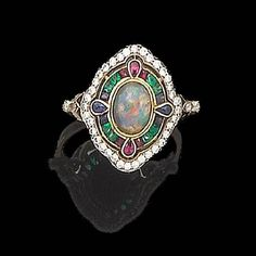 Centrally set with a cabochon opal surrounded by emeralds, rubies and sapphires within a further border of brilliant-cut diamonds,