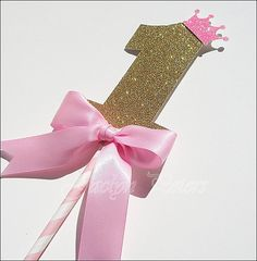 Our handmade baby girl's first birthday princess keepsake cake topper features a gold glitter number one with a pink glitter tiara, perfectly accented with a hand tied luxury pink satin ribbon bow. Fa