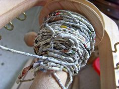Making newspaper yarn. This technique, using damp paper, sounds like it will work better. Plus using seeds for the yarn sounds like a neat idea too.