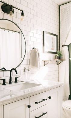 Bathroom Ceramic Tile Ideas for Your Walls White subway ceramic tile bathroom with marble countertop, round mirror and black hardware.White subway ceramic tile bathroom with marble countertop, round mirror and black hardware.