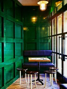 Emerald hallway with navy bench, industrial light fixture, and small dining table