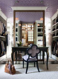 Chic purple closet design with purple walls paint color, textured purple ceiling, black vintage vanity desk, black quatrofoil chair with purple upholstery and shoe racks.