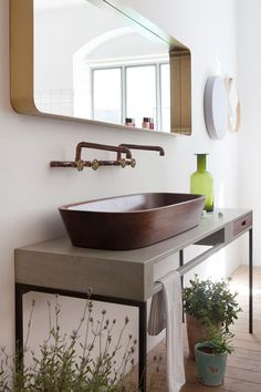 Plants in the bathroom create a spa-like feel. The double Shell basin, a seamless bowl carved from walnut, sits on a concrete table with its integrated towel rail and walnut drawer. Bathroom Basin, Small Bathroom, Small House Garden, Green Bathroom Accessories, White Laundry Rooms, Courtyard Design, Concrete Table, Home Scents, Timber Flooring