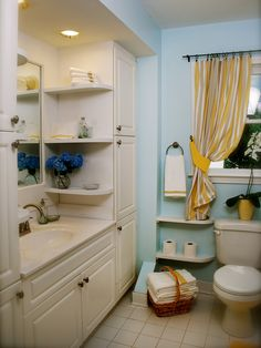 Small Space Storage - Small space doesn't have to mean zero storage. This bathroom vanity is surrounded by spacious cabinets and narrow display shelves beside the toilet and mirror for easy-to-reach necessities.