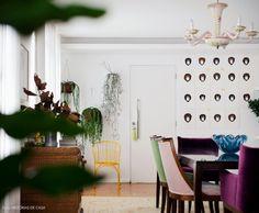 Vista da sala de jantar com parede verde de um lado e série de retratos de macacos feitos pelo morador, um dos proprietários da galeria BG27 (www.bg27.com.br)