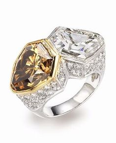 A fancy coloured diamond and diamond ring: Centring a shield-shaped fancy deep brown-yellow diamond, weighing 6.55 carats, and a shield-shaped diamond, weighing 6.79 carats, set against a ground of pavé-set brilliant-cut diamonds. Via Bonhams.
