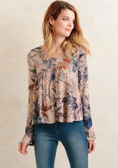 Effortless and breezy, this ethereal taupe blouse features a floral print in shades of teal, orange, and purple. The rounded neckline features a lace trim with embroidery detail along the bust an...