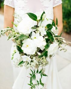 A trailing bouquet of garden roses, gardenias, clematis, olive branches, lily of the valley, seeded eucalyptus, and jasmine vines by Hello Darling @Natalie Walsh  @Martha Stewart Weddings Magazine