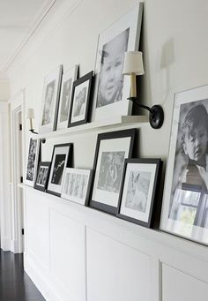 Extra wide trim topping the wainscoting creates space to display a gallery of images. A floating shelf adds another layer of images above. From Traditional Home Magazine. - Home Decor Home Improvement Projects, Home Projects, Photowall Ideas, Traditional Home Magazine, Creation Deco, Hallway Decorating, Decorating Tips, Blank Walls, House And Home Magazine