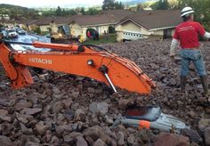 Earth moving equipment is buried by a debris flow in Camarillo Springs, Calif. about 50 miles northwest of Los Angeles on Friday, Dec. 12, 2014.