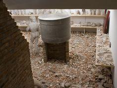 Lo que el fuego me trajo, 2008 Instalação Tijolos, cimento, cal, areia, entulho de demolição, madeira, barro, espelhos, vidro, sabão, conchas do mar, pára-brisa, capô Ford Escort, pins e adesivos. Galeria Ruth Benzacar