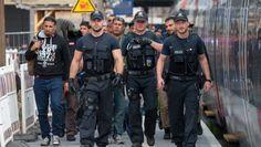 Polizeibeamte begleiten die überwiegend syrischen Flüchtlinge, die zuvor mit einem Zug aus Österreich in Passau angekommen sind.