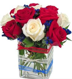 """Patriotic Rose Cube""  Delivery Conditions Reward Points Meaning of Roses Product Notes    Patriotic roses create a terrific display with red and white roses, accented with purple statice. The clear glass cube is accented with three stylish ribbons in red, white and blue. Celebrate Memorial Day, July 4th, Summer, and more by sending patriotic roses.    NOTE: This arrangement is a Zeidler's Flowers unique design and only available in the Evansville Metro area."