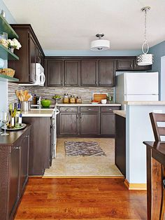 Oak cabinets were updated with gel stain in a rich espresso color to totally transform the kitchen. A contemporary glass-tile backsplash adds style, and sky blue walls bring calm color to the space. The color combination cont