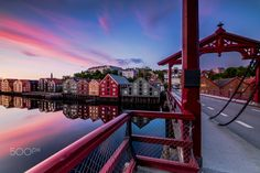 Midnight sunset over Gamlebybro, Bakklandet and Nidelva Trondheim  - This is a midnight sunset around 11:45 p.m. The picture has been taken over gamlebybro (the bridge with the red color). This is an iconic element of the Trondheim. Trondheim with picturesque, tiny, wooden houses. This idyllic neighbourhood on the east side of the Nidelva river features old timber buildings, originally the homes of the working class. Now restored, Bakklandet is a charming mixture of houses, shops and cafés…