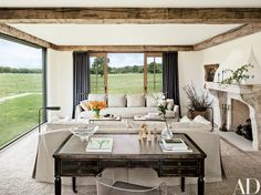 In the living room of the family's house, pasture views are framed by sliding doors curtained in a Sahco linen | archdigest.com